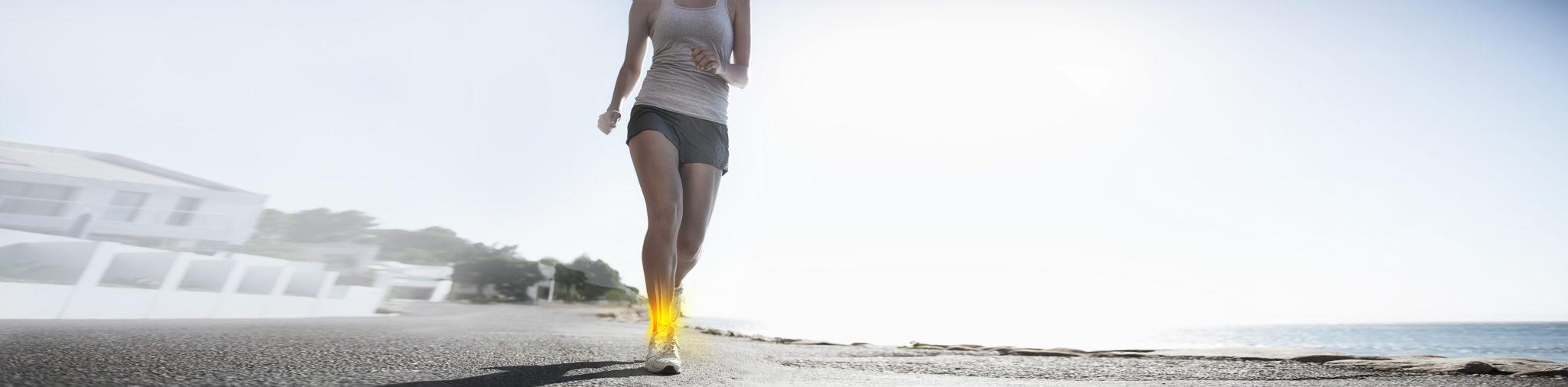 Eine laufende Frau mit einer gelb-orange leuchtenden Stelle auf Höhe des Schienbeins